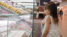 El muchacho hambriento del niño con la muchacha cerca de un escaparate de cristal con las galletas y los anillos de espuma eligen almacen de video