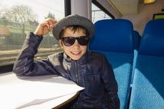 El muchacho hermoso con las gafas de sol monta en una lectura del tren del papel Fotografía de archivo libre de regalías