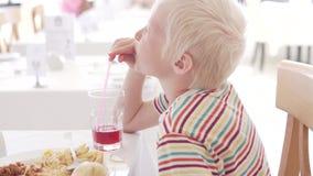 El muchacho hermoso del albino bebe el jugo de la cereza en un restaurante del hotel almacen de metraje de vídeo