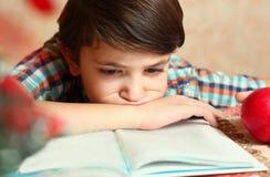 El muchacho hermoso del preadolescente que lee un libro y come la manzana Imagen de archivo libre de regalías