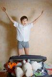 El muchacho hermoso del preadolescente salta con alegría con la anticipación del día de fiesta Foto de archivo