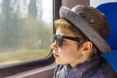 El muchacho hermoso en gafas de sol monta en un tren Imágenes de archivo libres de regalías