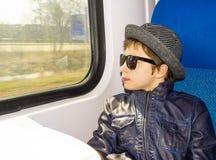 El muchacho hermoso en gafas de sol monta en un tren Foto de archivo libre de regalías