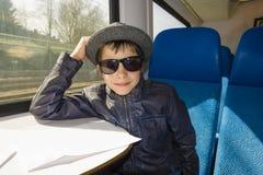 El muchacho hermoso en gafas de sol monta en un tren Imagenes de archivo