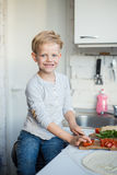 El muchacho hermoso está cocinando en la cocina en casa Alimento sano Imagen de archivo