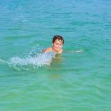 El muchacho hermoso goza el farfullar con su mano en el oce tropical Imagen de archivo libre de regalías