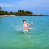 El muchacho hermoso goza el farfullar con su mano en el oce tropical Fotografía de archivo libre de regalías