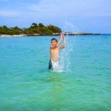 El muchacho hermoso goza el farfullar con su mano en el oce tropical Imagen de archivo