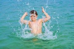 El muchacho hermoso goza el farfullar con su mano en el oce tropical Imágenes de archivo libres de regalías