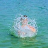 El muchacho hermoso goza el farfullar con su mano en el oce tropical Imagenes de archivo