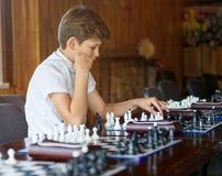 El muchacho hermoso lindo en la camiseta blanca juega a ajedrez con su rival en clase del ajedrez Concepto de la educación, juego fotos de archivo libres de regalías