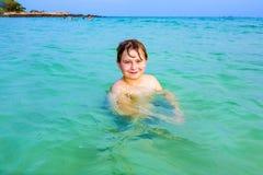 El muchacho hermoso se divierte en el océano Imagen de archivo libre de regalías