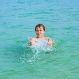 El muchacho hermoso se divierte en el océano y muestra los pulgares para arriba Imágenes de archivo libres de regalías