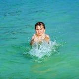 El muchacho hermoso se divierte en el océano y muestra los pulgares para arriba Imagen de archivo