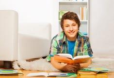 El muchacho hermoso sonriente hace la preparación en casa Imágenes de archivo libres de regalías
