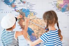 El muchacho hermoso y una muchacha en camisas rayadas del marinero miden distancia en mapa del mundo con la cinta métrica fotos de archivo libres de regalías