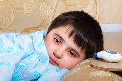 El muchacho hizo enfermedad y mentiras Fotografía de archivo libre de regalías