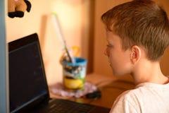 El muchacho imprime el texto en el teclado de ordenador en su sitio Fotos de archivo