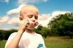 El muchacho infla burbujas de jabón en parque del verano Fotos de archivo libres de regalías