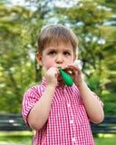 El muchacho infla el globo de goma, jugando en el parque en un backgr Fotos de archivo