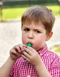 El muchacho infla el globo de goma, jugando en el parque en un backgr Fotos de archivo libres de regalías