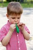 El muchacho infla el globo de goma, jugando en el parque en un backgr Imágenes de archivo libres de regalías