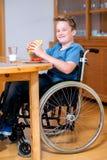 El muchacho inhabilitado sonriente en silla de ruedas está comiendo Fotos de archivo libres de regalías