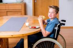 El muchacho inhabilitado sonriente en silla de ruedas está comiendo Fotos de archivo
