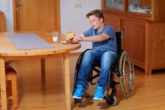 El muchacho inhabilitado sonriente en silla de ruedas está comiendo Fotografía de archivo
