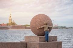 El muchacho intenta abrazar la bola de piedra enorme en St Petersburg Fotos de archivo