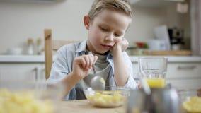 El muchacho intenta comer su menos plato del favor mientras que su madre añade el jugo a su hermana almacen de video