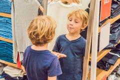 El muchacho intenta encendido la ropa en la tienda de la ropa de los niños Imagen de archivo libre de regalías