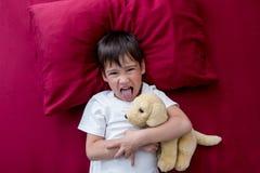 El muchacho irritable del niño rechaza irse a la cama imagen de archivo libre de regalías