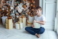 El muchacho joven abre un regalo debajo de un árbol de navidad fotos de archivo