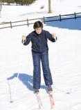 El muchacho joven aprende esquiar a campo través en los esquís Foto de archivo libre de regalías