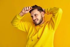El muchacho joven atractivo, sudadera con capucha amarilla que lleva, sonriendo y peinándose el pelo, hace el peinado solo, aisla imagenes de archivo