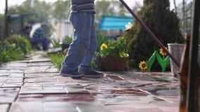 El muchacho joven ayuda a la familia que limpia la teja usando una fregona en jard?n C?mara lenta almacen de video