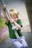 El muchacho joven balancea en una cuerda en el parque Fotografía de archivo libre de regalías