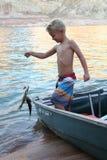 El muchacho joven coge un pescado Fotografía de archivo