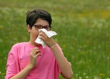 El muchacho joven con alergia sopla su nariz Fotografía de archivo libre de regalías