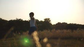 El muchacho joven con aumentado como aeroplano da el funcionamiento en hierba verde en el campo el día soleado Niño que activa en almacen de metraje de vídeo