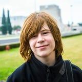 El muchacho joven con el pelo rojo está sonriendo Imagen de archivo libre de regalías