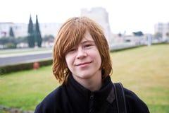El muchacho joven con el pelo rojo está sonriendo Foto de archivo libre de regalías