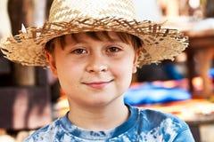 El muchacho joven con el sombrero de paja es feliz Imagen de archivo libre de regalías