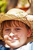 El muchacho joven con el sombrero de paja es feliz Foto de archivo libre de regalías