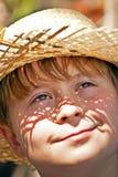 El muchacho joven con el sombrero de paja es feliz Fotos de archivo