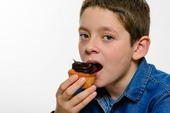 El muchacho joven con la magdalena del chocolate del eatng de la camisa del dril de algodón, en blanco aisló el fondo Cierre para Imagen de archivo
