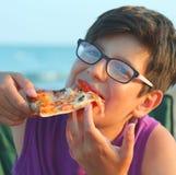 El muchacho joven con los vidrios come una rebanada de pizza en la playa Fotografía de archivo