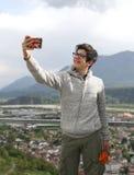El muchacho joven con smartphone moderno hace un selfie Imagen de archivo libre de regalías