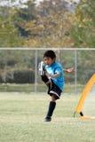 El muchacho joven con un grande golpea adentro fútbol con el pie Foto de archivo